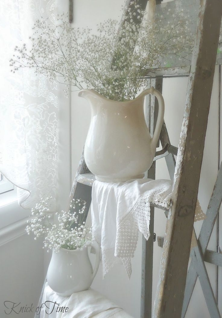 vintage ladder and linens with white ironstone pitchers. baby's breath makes it feel like spring