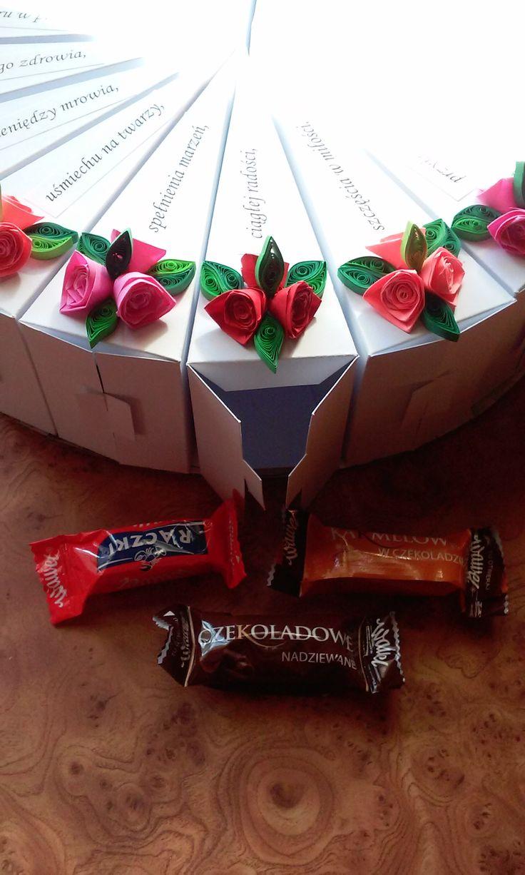 Tort z papieru jako prezent na 18 urodziny, 18 kawałków podzieliłam na 3 wyszło po 6 części, w sześciu są czekoladki - żeby dorosłe życie było słodkie, w następnych 6 są zdrapki lotto żeby miała szczęście, a w ostatnich 6 małe prezenciki i przestrogi na start w dorosłość. Na górze jest kosz z 18 różami, butelką wódki i lizakami.