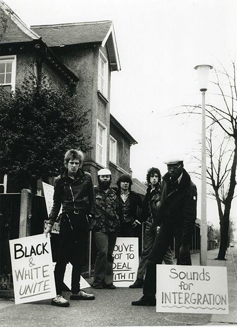 """theunderestimator: """" Paul Simonon & Mick Jones of The Clash, Glen Matlock of The Sex Pistols & members of Steel Pulse demonstrating outside National Front Leader Martin Webster's house in 1977..."""