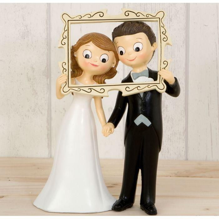 Graciosa figura de novios para la tarta de boda en la que los novios posan asomándose por un marco