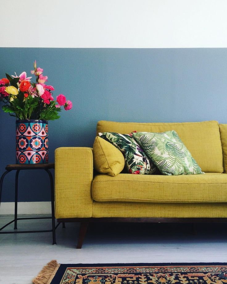 Half painted wall in Flexa denim drift, mustard yellow Torino couch (Wehkamp), fake flowers in a large vintage tin and cushions with a botanical print. #interior