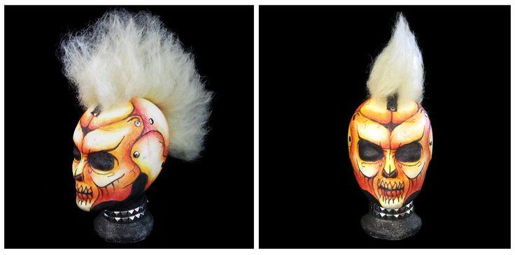Maquillaje de calavera realizado sobre cabeza de porexpan en tonos cálidos, con decoraciones de pinchos, tornillos y pelo con crepé