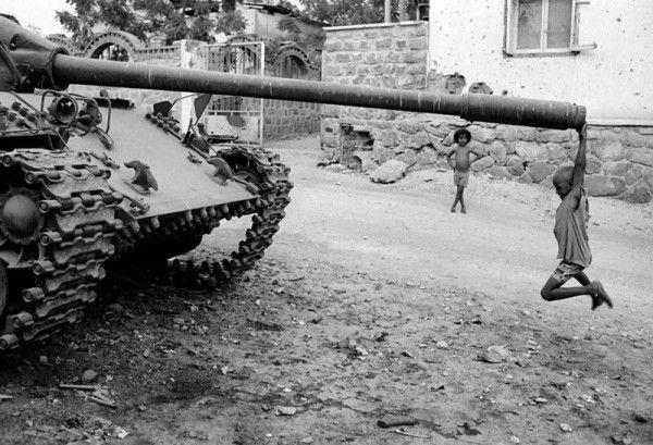 Um garoto africano brinca com um tanque de guerra abandonado, 1991.