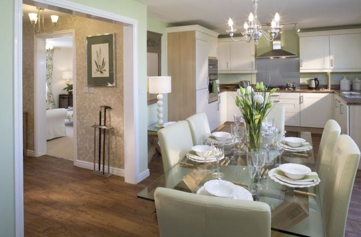 Interior designed kitchen dining room using an Eau de nil and chalk white colour scheme, oak flooring and oak work tops - beautiful pale pastel sherbet green linen upholstered dining chairs with the perfect glass table with a hint of glacier green, with an open plan hall way.