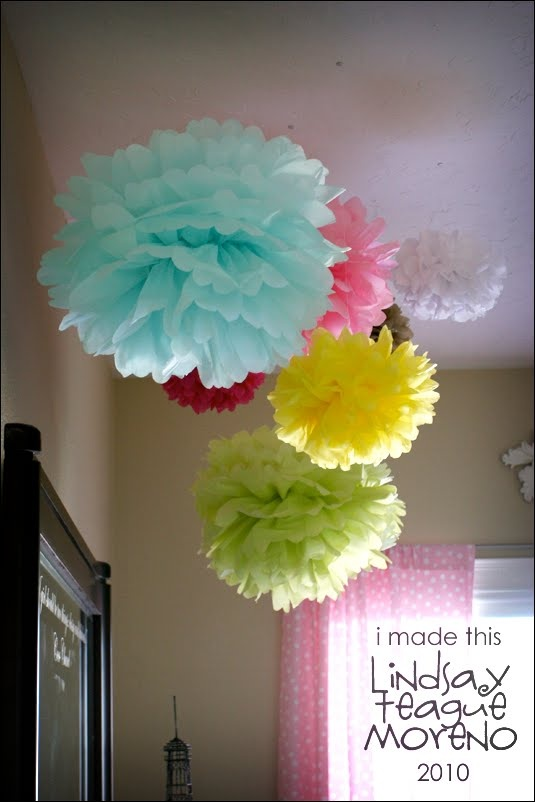 Tissue paper pom poms hanging from ceiling create a for Hanging pom poms from ceiling