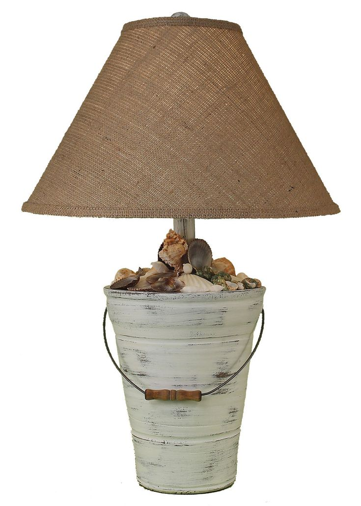 "Enjoy this 27.5"""" Bucket of Shells beach cottage lamp! Created with a soft distressed off-white finish, and complete with real seashells decorating the top of the lamp base and metal detailed handle."