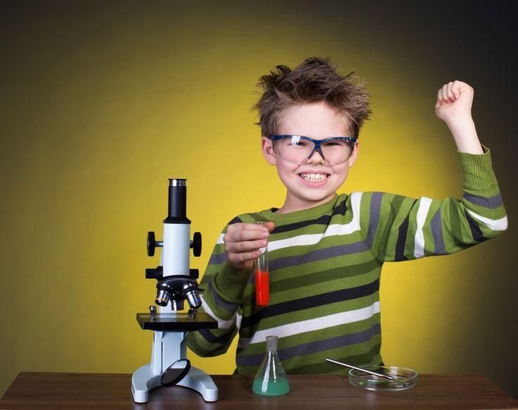 Junge spielt mit Mikroskop und Glaskolben