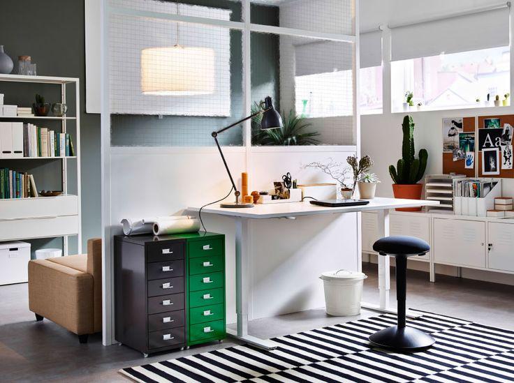 Espace de travail avec bureau blanc réglable en hauteur. Un tabouret haut noir et des caissons à tiroirs gris et vert complètent l'ensemble.