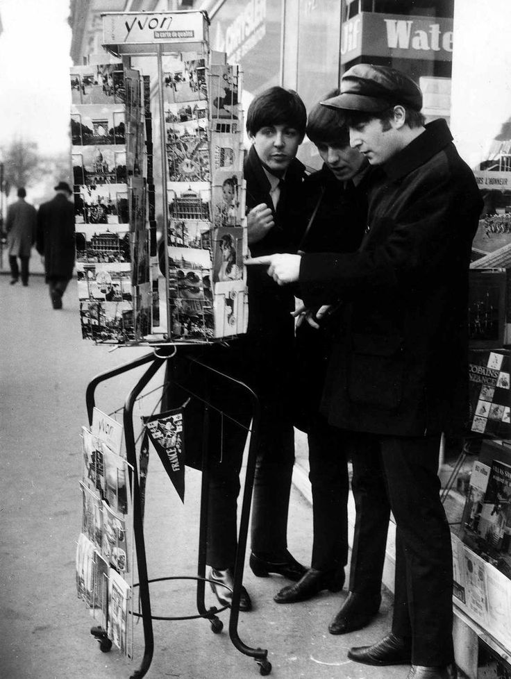 Paul McCartney, George Harrison and John Lennon of the Beatles pop group looking at postcards