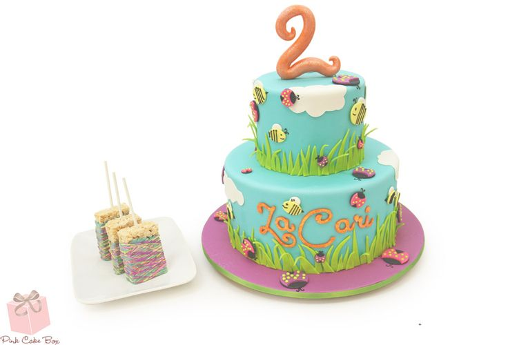 Ladybugs and bees are a cute combination for a birthday party and we incorporated both insects into this 2nd birthday cake. The cake is covered in sky blue fondant with clouds and green blades of grass. Crawling around each tier are an assortment of different colored ladybugs and bees.