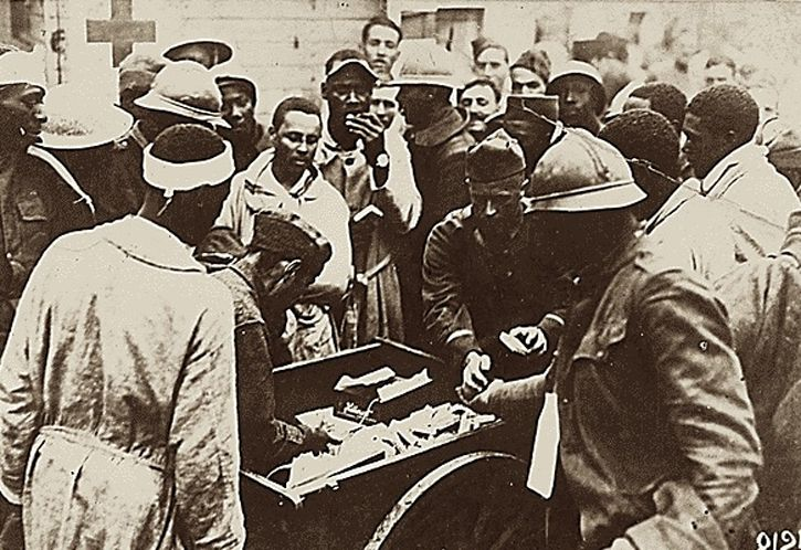 American wounded in France. American Red Cross workers distribute chocolate, cigarettes et cetera to the wounded Negro soldiers arriving at American Red Cross military hospital Number 5 at Auteuil, France.