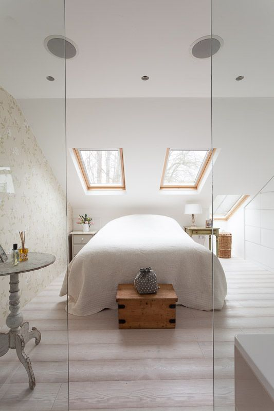 Clever design in this master bedroom maximises the use of space in the eaves of this loft conversion, glass partitions separate the ensuite from the master bedroom while keeping maintaining a feeling of openess.