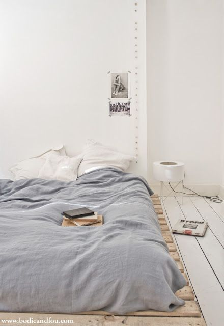 Mattress elevated onto 'found' wooden palettes - on painted white floor and simple linens