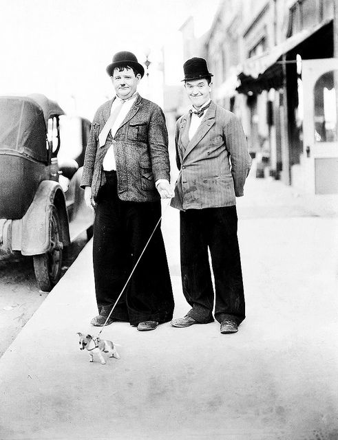 Oliver Hardy and Stan Laurel with a tiny little friend in a publicity photo, 1932