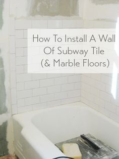 Installing a wall of subway tile and marble floors (makes such a giant difference!)