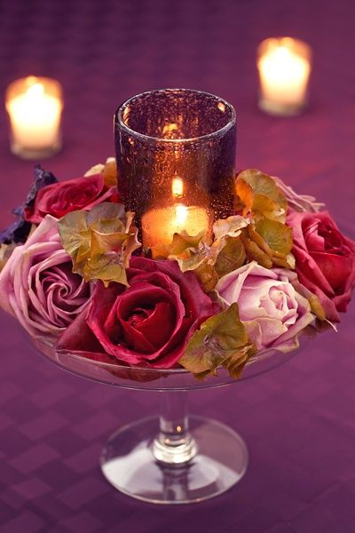 candle in glass votive surrounded by roses arranged in a pedestal bowl or on  a cake stand