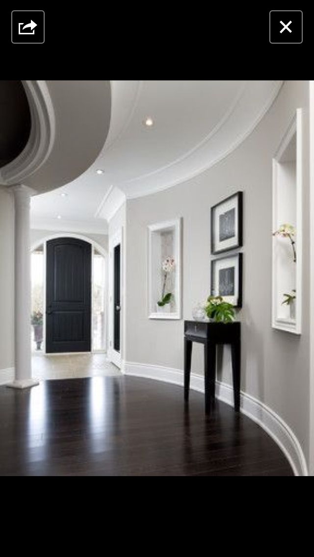 Light gray walls white trim dark floors in this stunning foyer molding and curved walls my colors for sure