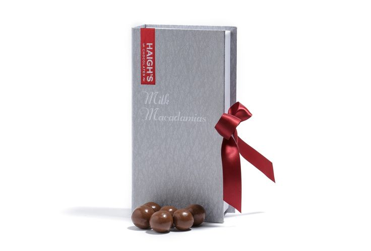 Haigh's Chocolates –Milk Roasted Macadamias  Whole roasted #Australian macadamias, pan coated in layers of milk chocolate in a ribboned silver book box.  #HaighsOnline #Christmas #Chocolate #Gifts