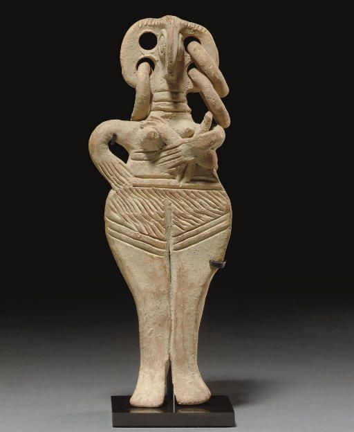 Cypriot terracotta female figure with infant, Late Cypriot II, 1450-1200 B.C.Stylized standing figure depicted nude, with a birdlike face and pellet eyes, the ears each pierced twice, three hoop earrings preserved, the body flat, with wide hips, the large pubic area hatched, her pointed breasts high on her chest, with several decorative horizontal grooves on the body, her right hand akimbo, the left arm cradling the infant, 15.2 cm high. Private collection