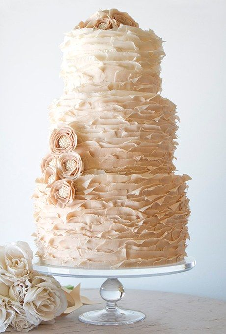 """For a unique take on the fondant ruffles trend, Sherri Meyers of The Pastry Studio layered the sugar frills to create a """"peeling"""" effect, which gives the design an aged, antique look. Inside, you'll find hazelnut-praline cake; the cake is finished with sugar flowers with ivory beaded centers."""
