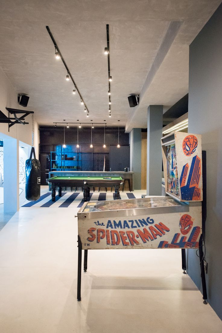 """The ultimate man cave! We converted the unused lounge area of a Cape Town residence into an industrial-inspired dream pad for the family's teenage boy and his friends. The design includes impressive design elements, such as a fully functional skate bowl, mammoth timber """"wave"""" and a four-and-a-half-metre bar!  #InhouseBrandArchitects #mancave #interiordesign #pooltable #pinball"""