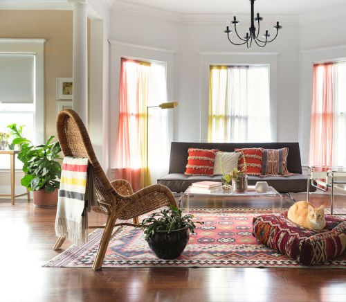 """""""The living room ended up orange somehow, which is funny because it's not one of my favorite colors, but I love the rich textiles and warm lighting,"""" says Emily. """"It feels a bit 70s to me and like stumbling into a quirky cabin. Our diva cat Arnie has taken ownership of our Turkish pouf."""""""
