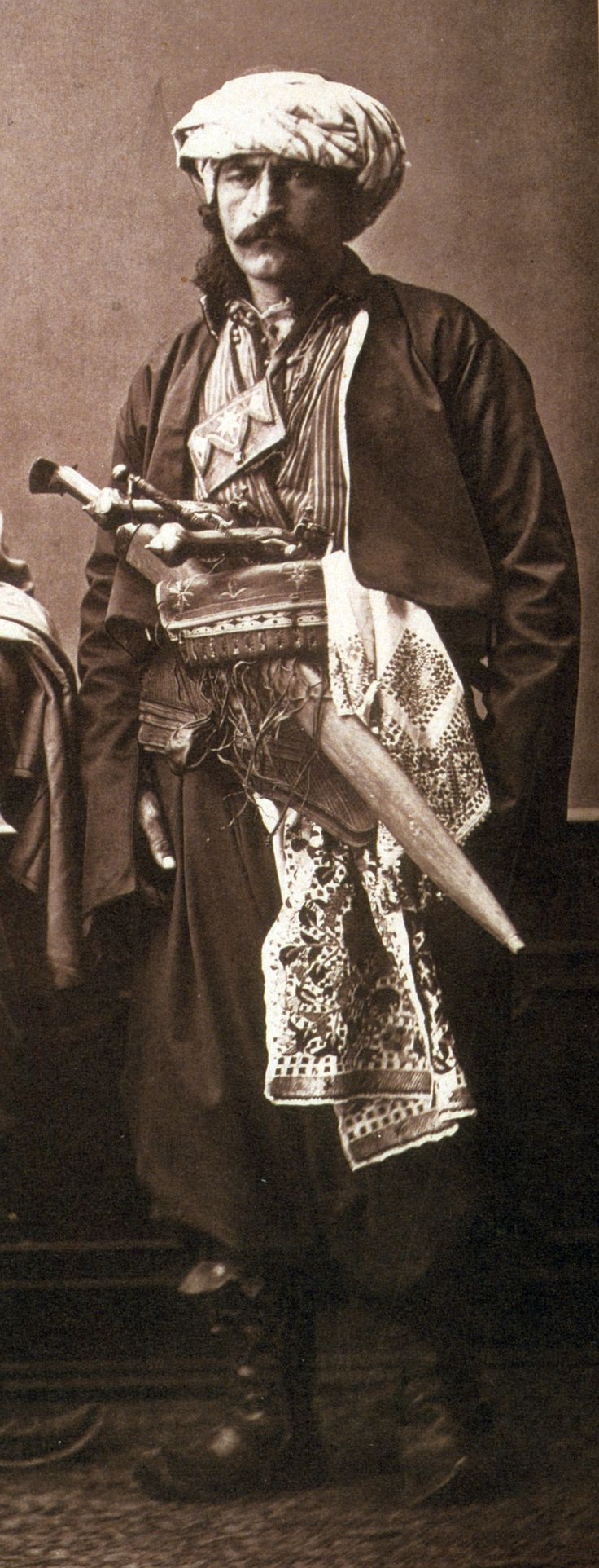 "Ottoman cavalry from Koniah, voluntary auxiliaries used concurrently with the Zaptîes (gendarmes) as escorts to authorities, pilgrims, travelers, to carry orders, to protect convoys of goods. Shown with a silahlik (weapons belt) holding a large yatagan and two pistols (kuber) in a holster (kuberluk). From:Les costumes populaires de la Turquie en 1873, 74 photographic plates by Pascal Sebah, published by the Imperial Ottoman Commission for the ""Exposition Universelle"" of Vienna in 1873."