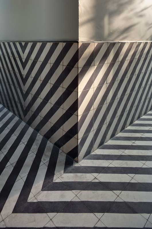 Incredible striped floor, half wall. Reminds me of an old episode of the Avengers, Emma Peel keeps walking into the same room one room rotates so she opens the same door over and over then she walks into one of those spiral optical illusion tunnels..  I love this,  add some mirrors and Poof!  Dazed and Confused....