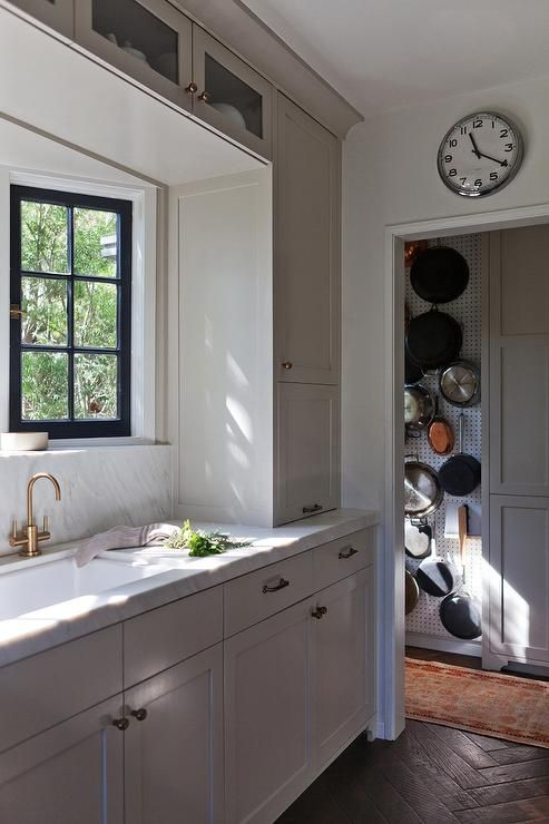 Beautiful kitchen features light grey shaker cabinets adorned with brass hardware topped with white marble fitted with a white porcelain sink and brass gooseneck faucet under a bay window.