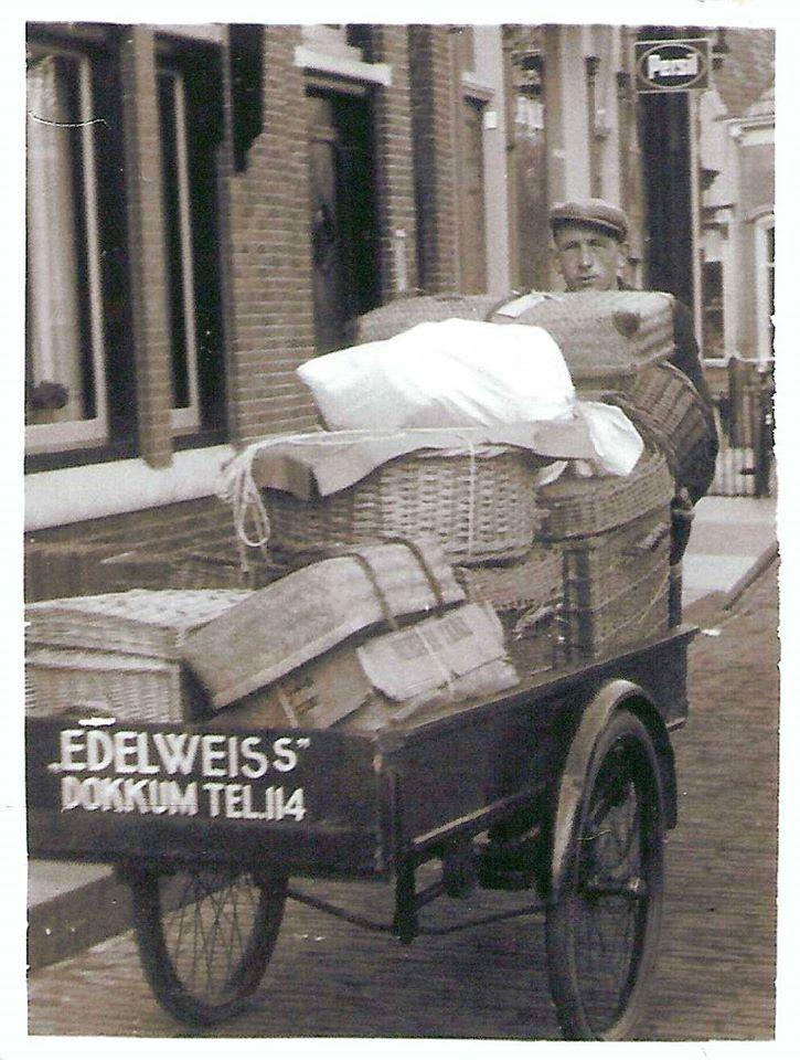 """Dit is Rienk Kooistra die snel nog even wat manden wasgoed van Wasserij """"Edelweiss"""", gevestigd aan de Oostersingel, naar de Vrachtrijders of vrachtboten brengt. Of naar klanten in dokkum natuurlijk. Dit was denk ik er even snel tussendoor, want zijn eigenlijke werk was in de wasserij zelf. De stoomketel en de machines bedienen, was sorteren, wassen enz. Hij was daar lang de man die elke dag als eerste begon en en de laatste die wegging. Kooistra werkte bij deze wasserij van 1926 tot 1975."""