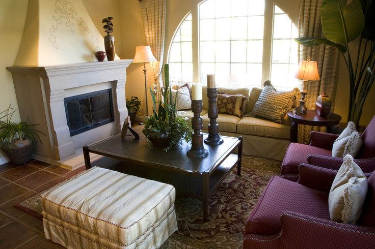 Here's another cozy living room fitting a stone fireplace, patterned rug over brown tile floor, red chairs and large, two-level coffee table.