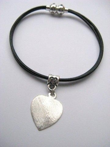Zwart lederen armband met magneetslot en een metalen bedeltje in de vorm van een hartje.