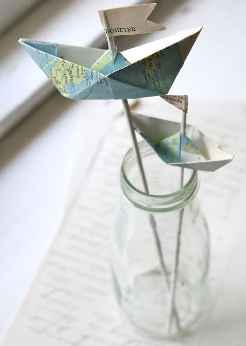 How to fold nautical paper boats by Jenny Doh. Once the boats are folded, paint bamboo skewers with white acylic paint and poke them into the boats from the bottom. Cut pieces of book pages to create flags and adhere to the tips of the bamboo skewers.
