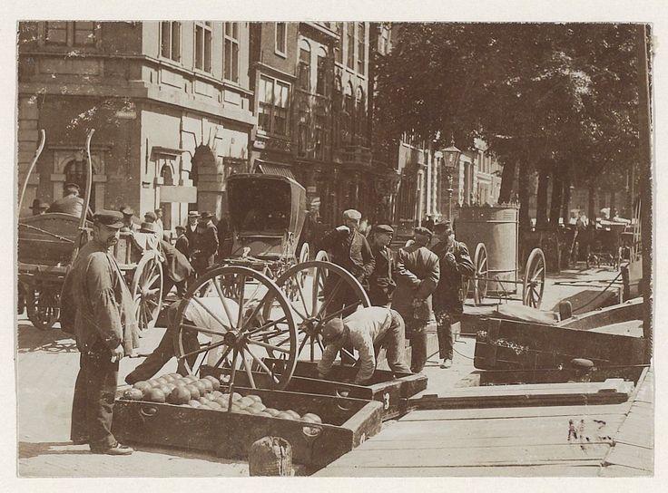 Damstraat met kaasmarkt. Per schip en kaasbrik zijn Edammer kazen aangevoerd. Deze worden in weegbakken geladen en naar de Waag vervoerd.                               Foto 1901                               Fotograaf: Anoniem