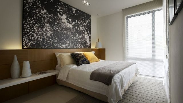 kleines schlafzimmer betthaupt holzplatten indirekte beleuchtung schwarz weiße kunst wand