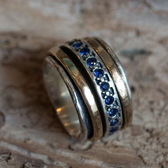 Sans cesse ~~~~~~~~~~~~~~~~~~ C'est un de nos nouveaux anneaux de la méditation. La base de cette bague est en argent sterling oxydé et détient trois bandes spinner sur le dessus. Le spinner central est en argent sterling sertie de pierres de corindon saphir petit dispersées entre un motif continu. Les deux autres fileuses sont martelés or jaune rempli, assis de chaque côté de la bande centrale de rubis et argentée. R1075L-5 © 2011 Artisanimpact Inc. Tous droits réservés.  Construction & ...