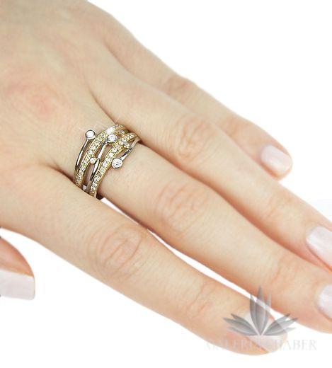 Ciekawy pierścionek wykonany ze złota próby 333. W wyrobie osadzono cyrkonie, dodatkowo ozdabiając je elementami z białego złota. Wzór nowoczesny, ciekawy, o szerokości około 1,2 cm.