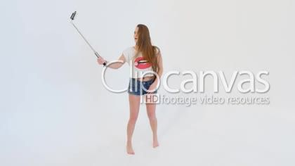 Beautiful Young Woman Taking Selfies in Studio HD Stock Footage Clip. Medium shot. 2016-01-21, RUSSIAN FEDERATION.