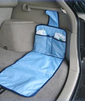 Photo of the Dipe-N-Go baby changing station in a car consisting of a blue diaper pad with pockets.