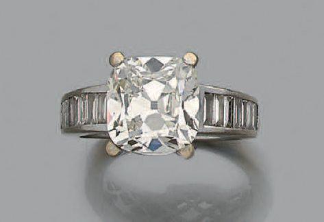 #Bague en or gris 18k ornée d'un diamant de taille ancienne de forme carrée épaulé de diamants baguettes  Poids du diamant central: env 5.03 cts  Pb.:9.4 gr    A white gold ring set with an old-cut diamond… - Aguttes - 16/03/2017