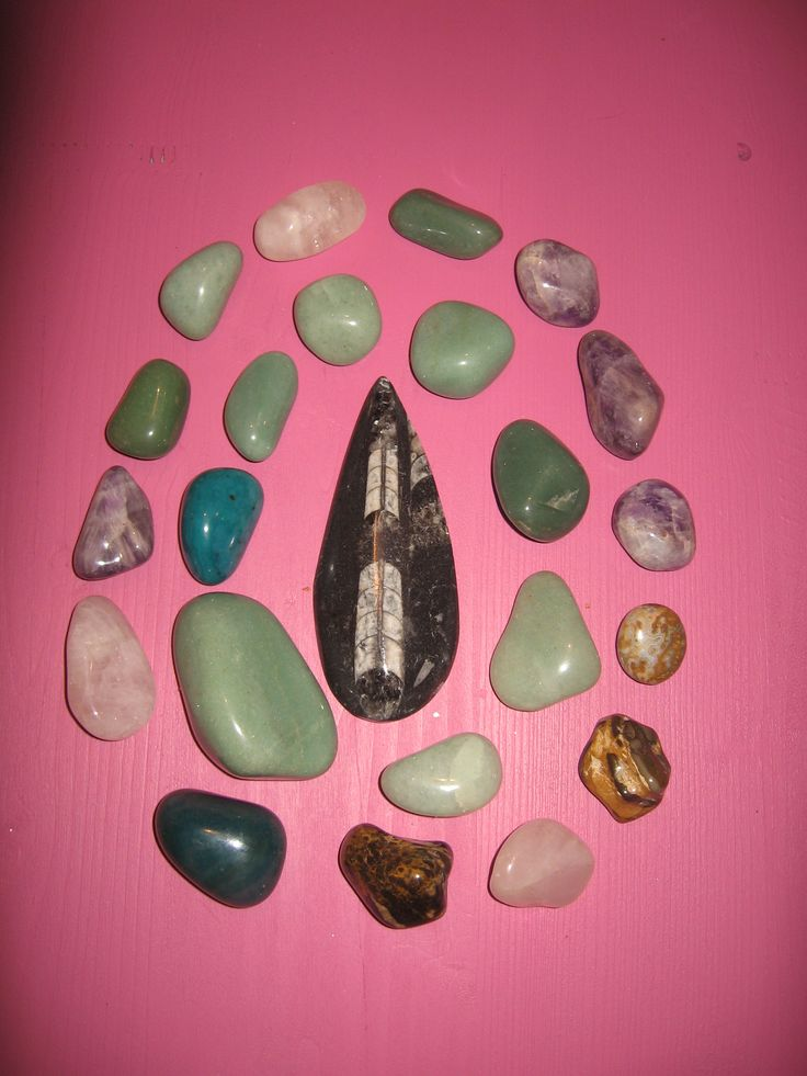 Polished gemstones: aventurine, ametyst, pink quartz, jasper, tiger's eye and fossil in the center.