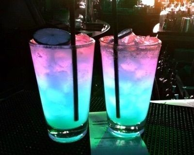 Glowing drinks  Astro Pop. 1 oz Vodka & 1 oz Sour mix. Shake with ice & strain into cup. 1/2 oz Grenadine slowly poured down side. Then 1/2 oz Blue Curaçao slowly down side. They will layer..