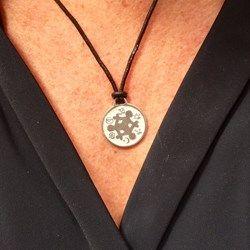 De metalen amulet hangt aan een stoer donkerbruinleren koord en is verstelbaar van 34 cm. tot 69 cm.  De symbolen die op de voorzijde van de amulet staan zijn: Boeddhisme,Atheïsme,Hindoeïsme, Jodendom,Christendom ...