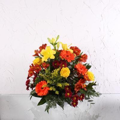 Centro Alegría - Un centro de flores cálido y clásico. Este centro de flores tiene rosas, gerberas, margaritas, y astromelias | Bourguignon Floristas