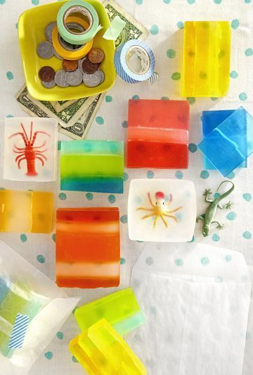 """Grease insides of clean, pint-size milk cartons or small juice boxes with cooking spray. For each layer, melt 3 or 4 1-oz. cubes of soap in a glass measuring cup in the microwave for 25 seconds. Add a drop of food coloring, stir, and melt again for 10 seconds more. Pour the warm mixture into prepared containers; let cool. Repeat, letting each colored layer solidify before pouring the next. Cut individual bars once they've cooled. For toy soaps, fill a container with ½"""" of melted..."""