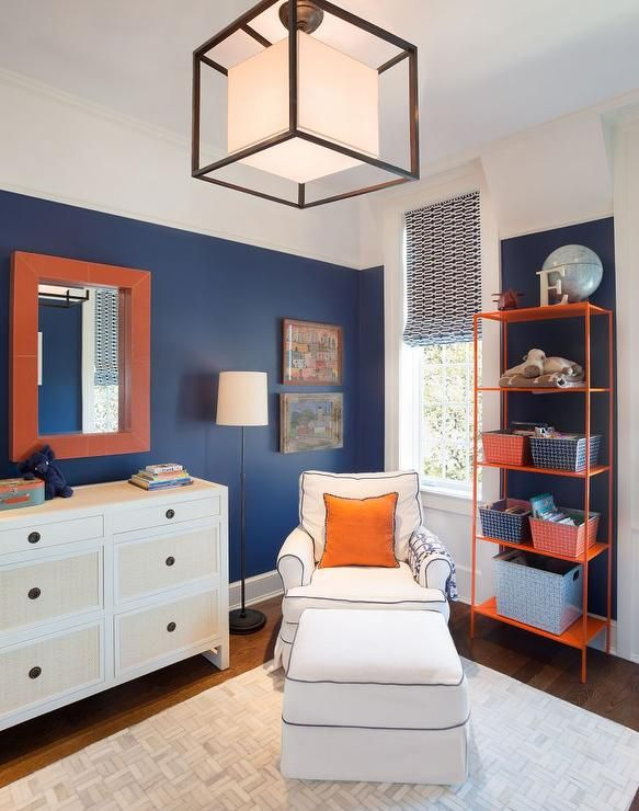 Navy and orange kid's bedroom features walls painted navy lined with an orange mirror over a white ...