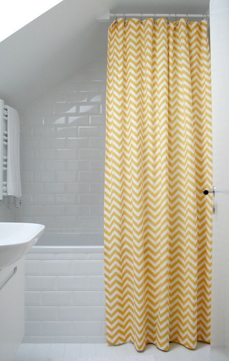 Yellow chevron showercurtain and white clean tile