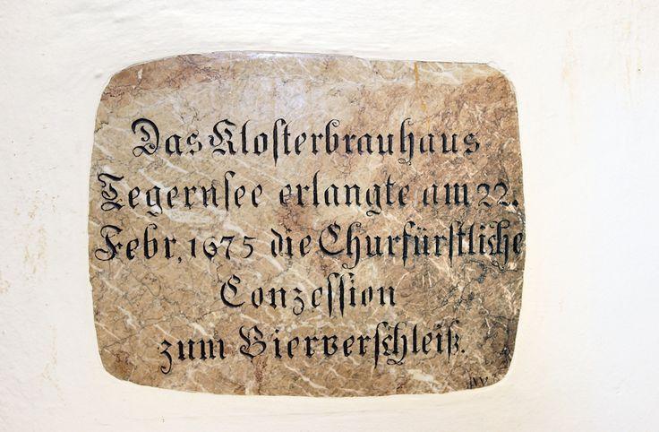 """Die Jahreszahl auf der Gedenktafel neben der Schänke führt in die Regierungszeit von Tegernsees großem Abt Bernhard Wenzl, der aus der Nähe von Salzburg stammte und das Kloster Tegernsee von 1673 bis zum Jahr 1700 leitete. Am 22. Februar 1675 war es soweit: Das Kloster erhielt die ersehnte """"Churfürstliche Conzession zum Bierverschleiß"""" in Tegernsee."""