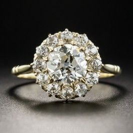 Dating back to the first or second decade of the twentieth-century, at arm's length this classic halo ring, featuring a bright-white and brilliant 1.29 carat European-cut diamond, has the look and circumference of a 5 carat diamond. The gorgeous stone, accompanied by a GIA Diamond Grading Report stating: I color - SI2 clarity, is encircled by a dozen small sizzling European-cut diamonds for an ultra-sparkling effect. A stunning vintage classic, currently ring size 6.