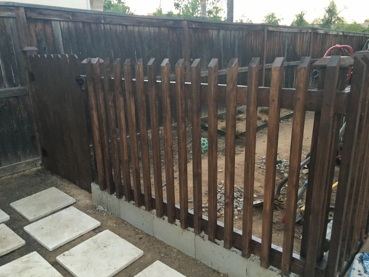 Made a fence out of wood and used cinder blocks as the foundation. Stained the wood and purchased hardware at Home Depot for the door.